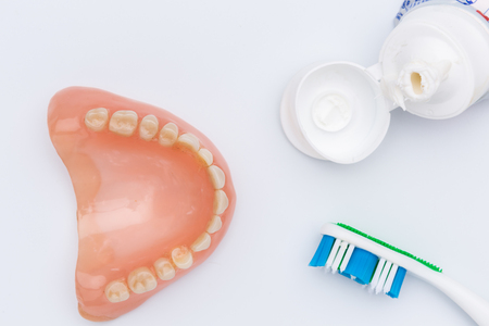 denture with tooth brush and toothpaste, top view, on white background, closeup, dental prothesis, teeth care