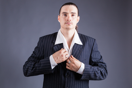 Young male confident male posing in gangster style suite. Studio isolated on gray background. 스톡 콘텐츠