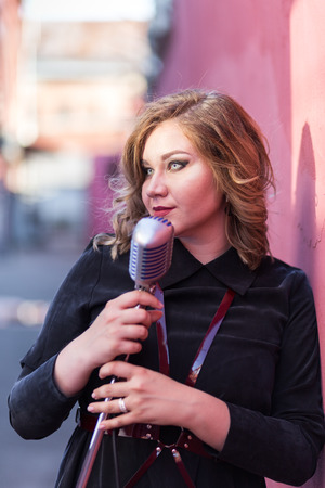 Beautiful sexy woman in dark velvet dress singing with the retro style microphone on pink background 写真素材