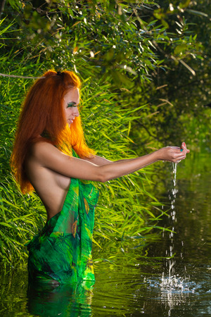Naked in the river. portrait of beautiful half dressed red hair woman enjoys the waters of a river at sunny hot summer day