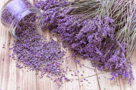 lavender dried flowers in glass jar and scattered and bunch on rustic wooden background top view closeup Stock Photo