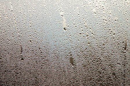 Raindrops on the fogged glass with gray background