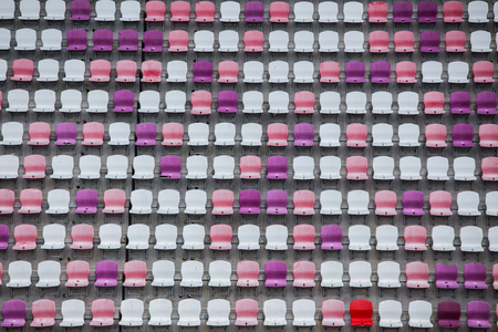 multi-colored rows of empty seats in football stadium background