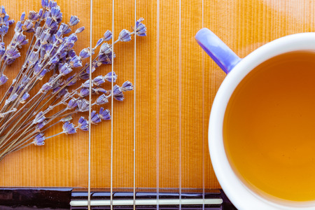 A musical instrument acoustic guitar, yellow wood deck with strings decorated with dried bunch of lavender flowers and cup of herbal tea, closeup, fragment, top view. concept of music and nature.