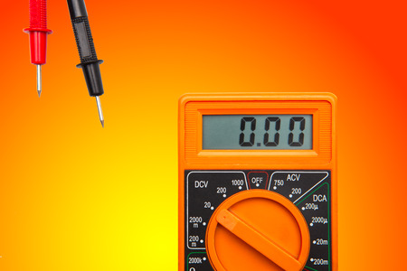 orange color electric Multimeter device on gradient yellow orange background Banque d'images