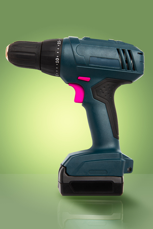 Cordless battery powered green drill with pink buttons on gradient green background with reflection on surface