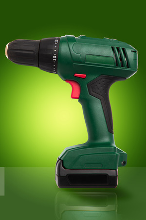 Cordless battery powered green drill with red buttons on gradient green background with reflection on surface