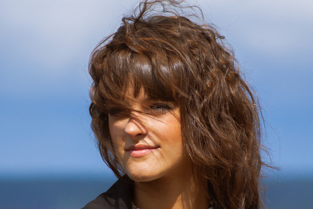 closeup portrait of beautiful smiling woman in black jacket, with long dark brown curly hair outdoor at sunny windy day, on blue sky background looking into the camera