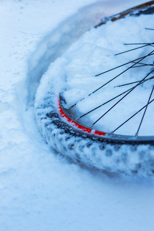 closeup of bicycle wheel with spokes lying in snow partly covered. selective focus, shallow depth of field, all weather winter cycling, extreme outdoor Stockfoto