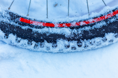 closeup of bicycle wheel with spokes lying in snow partly covered. selective focus, shallow depth of field, all weather winter cycling, extreme outdoor Banque d'images