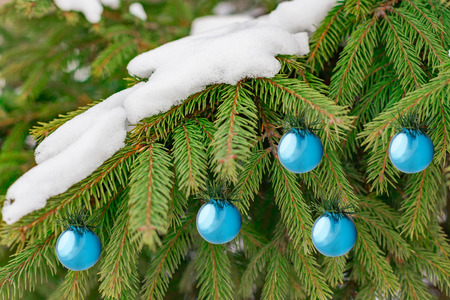 Christmas Background with blue glass glossy decoration balls and snow on beautiful green pine tree brunch closeup, selective focus, Copy space. Banque d'images
