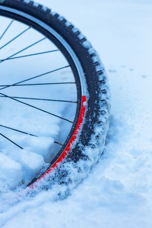 closeup of bicycle wheel with spokes lying in snow partly covered. selective focus, shallow depth of field, all weather winter cycling, extreme outdoor Stok Fotoğraf