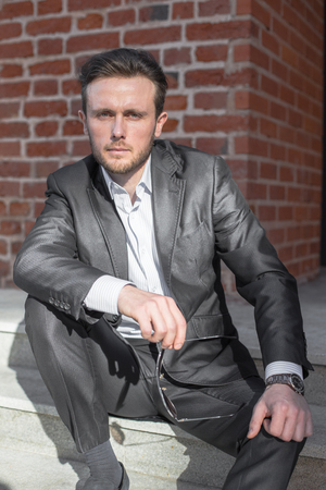 Half length portrait of young sniling man in suit sitting on steps outside of his office building, prosperous male leader after business meeting
