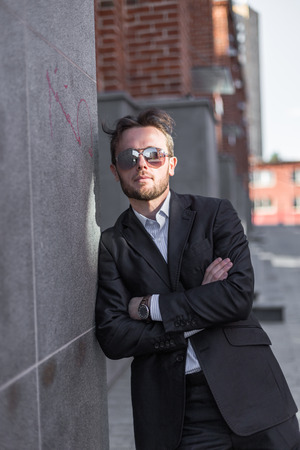 Half length portrait of young confident man in suit and sunglasses standing outside of his office building, prosperous male leader after business meeting