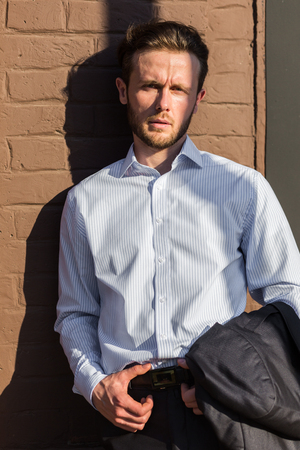 Half length portrait of young businessman dressed in suit with jacket in his hands on sunny hot day in modern architecture surrounding
