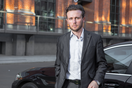 Attractive successful young businessman in a business suit near his car premium class car and office buildings in background Banque d'images