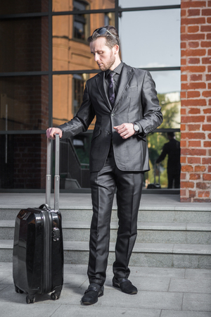 Business trip, traveling, luggage and people concept - Portrait of a handsome businessman in suit with travel bag over airport background