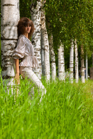 Portrait of attractive dark-haired young woman wearing light clothes in birch forest at summer day