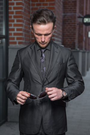 Half length portrait of young confident man manager standing outside of his office building, prosperous male leader dressed in suit after business meeting Banque d'images