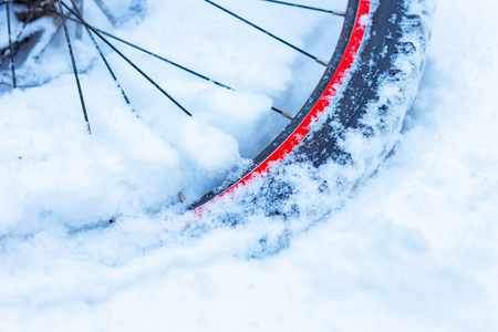 closeup of bicycle wheel with spokes, chain and transmission parts lying in snow partly covered. selective focus, shallow depth of field, all weather winter cycling, extreme outdoor
