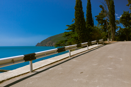 The scenic coastal asphalt road and turquois sea water and blue sky behind