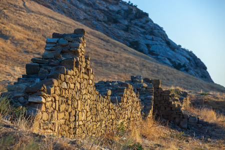 shot of a stone wall and window old ancient ruins on a hill in sunset light, Crimea, Ukraine