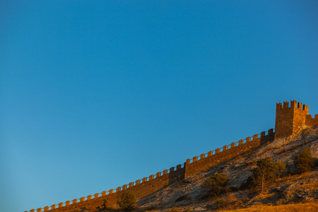 shot of a stone wall old ancient ruins on top of a hill in sunset light, Sudak, Crimea, Ukraine
