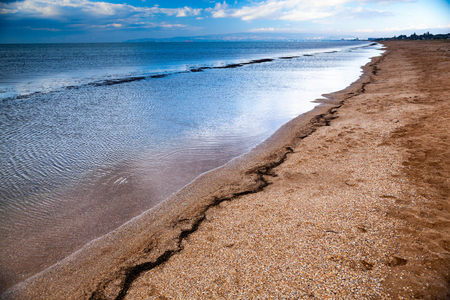 dramatic scenery empty long sandy beach with shallow water and cloudy storm sky, Crimea, Ukraine