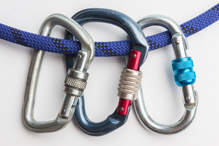 old used metal carabines in scratches on a rope for mountaineering on white background. Climbing concept Stock fotó