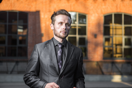 Half length portrait of young confident man manager standing outside of his office building, prosperous male leader dressed in suit after business meeting Stock fotó