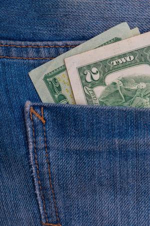 two Dollar banknotes in blue jeans rear pocket closeup