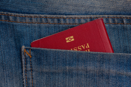 Red biometric passport in blue jeans pocket closeup
