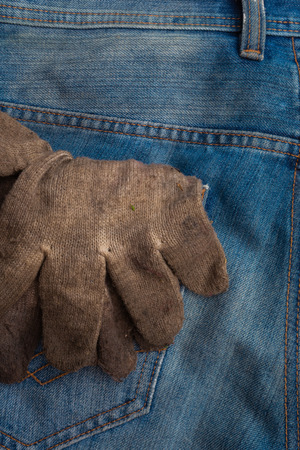 dirty cotton protective gloves in worker blue jeans rear pocket background