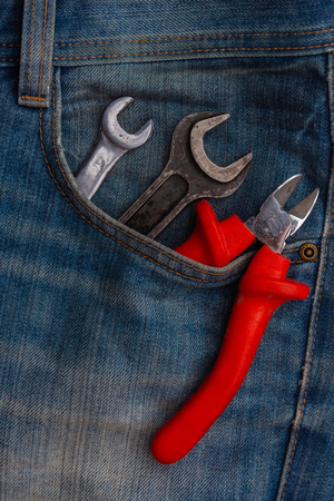Wrenches and plier tools in blue jeans pocket closeup