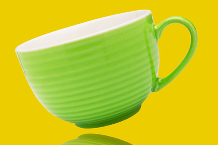 green clean porcelain tea or coffee cup mug isolated on yellow with reflection under it on surface, front view Stock fotó