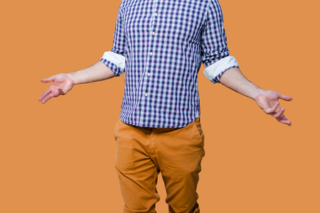 half length portrait without face visible wearing checked pattern shirt and orange trousers, with his hands showing confussion or surprise emotions isolated on orange Stock fotó