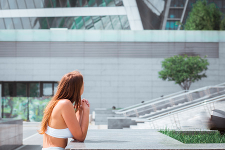 Beautiful hipster girl with long hair in white clothes is standing near the modern architecture building at sunny day, looking at building, face is not visible