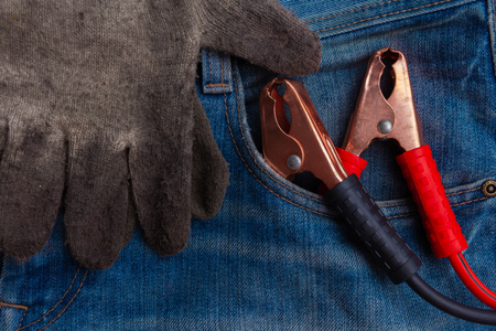 metal electric red and black clamps and dirty protective gloves for emergency car start in blue jeans pocket closeup