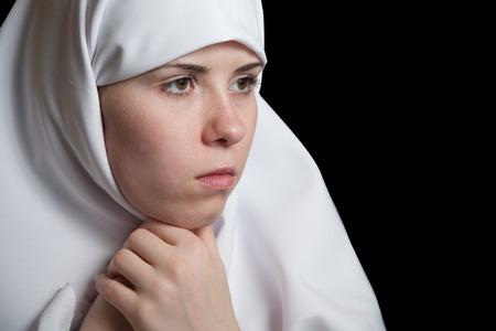 Junge Nonne im weißen Kleid, Gesichtsnahaufnahmeporträt lokalisiert auf Schwarzem Standard-Bild