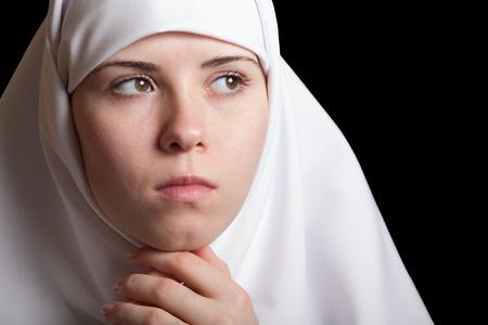 Junge Nonne im weißen Kleid, Gesichtsnahaufnahmeporträt lokalisiert auf Schwarzem