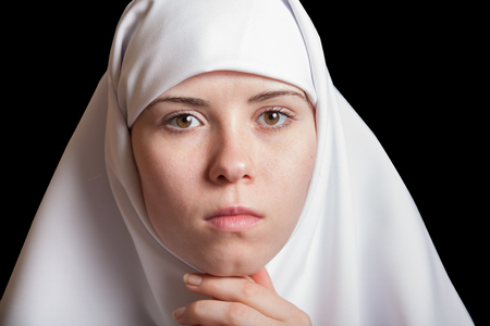 Young nun in white dress, facial closeup portrait isolated on black
