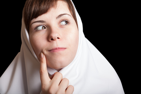 young woman funny dreaming meditating nun in white isolated on black background facial portrait