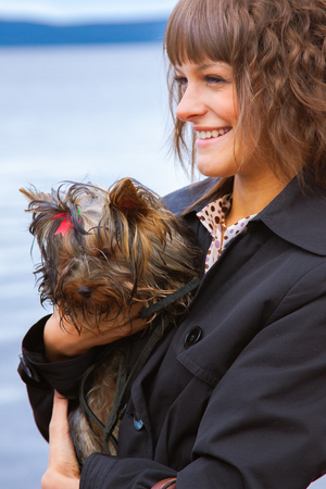 portrait of pretty young woman with long curly hair in black jacket holding tiny Yorkshire Terrier dog closeup on blue sky background Stock fotó
