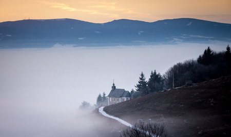 Foggy winter dusk with chapel on the hillside