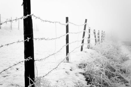 Frosty winter day with fiered fence in the foreground Stock Photo