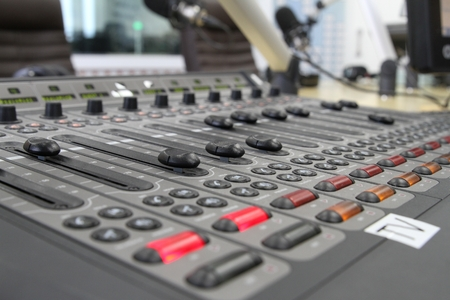 objectivity: Professional audio operator working on audio mixer knobs during live TV telecast