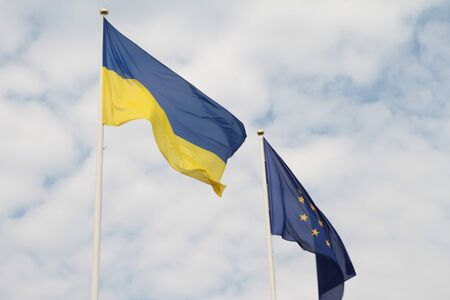 Flags of European Union and Ukraine waving on flagpoles isolated on white background.