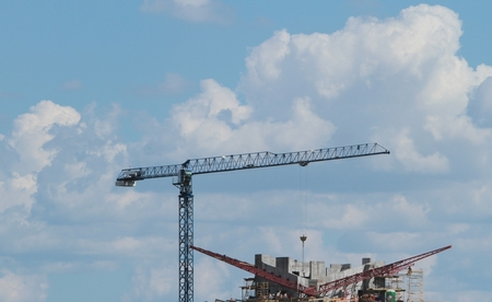 Building crane and building under construction against blue sky. Stock Photo