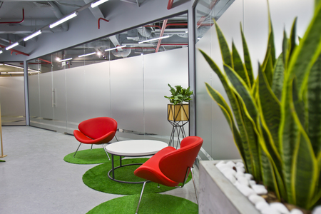 A luxurious sitting area in a small office with a modern interior design. Modern Interior of Cafe with Red Chairs and Green Plants