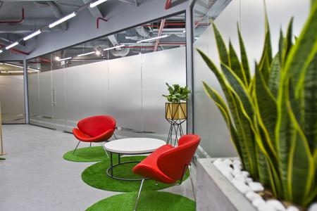 Un coin salon luxueux dans un petit bureau avec un design intérieur moderne. Intérieur moderne du café avec des chaises rouges et des plantes vertes
